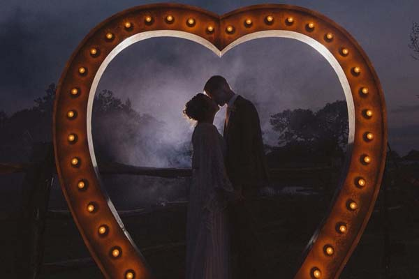 wedding couple under large light up heart